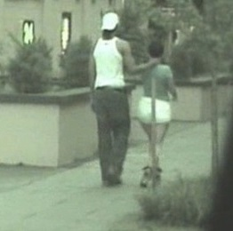 Pimp walking with one of his victims with a hand around the back of her neck.