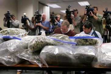 Image of TV cameras aimed at bags of pot