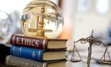 Image of a clear globe with a scale inside it that sits on top of books with the titles Ethics, Civil Code, and Constitutional Law.